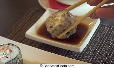 Sushi rolls dipped in soy sauce with chopsticks