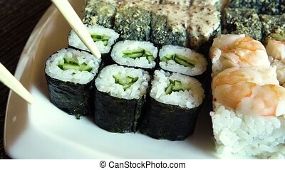 Female hand takes sushi rolls - Female hand takes rolls of...
