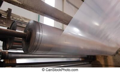 Plastic sheet curled on a roll at the factory - Industrial...