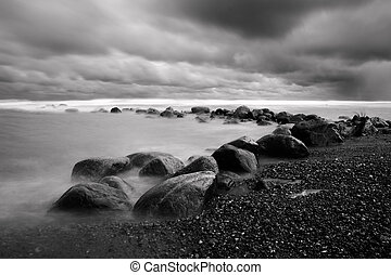 Dramatic landscape with rock coast and bad weather clouds in...