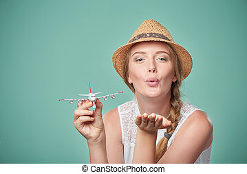 Woman in straw hat holding airplane model in hand - Travel...