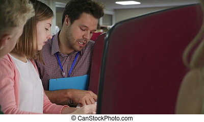 One To One Lesson - Teen student working with her teacher on...