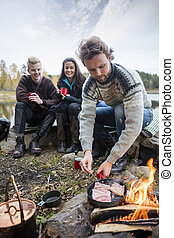 Man Cooking Food On Campfire With Friends In Background -...