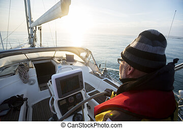 Man Steering Yacht At Helm During Sunset - Mature man...