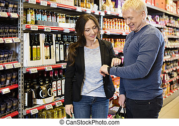 Smiling Couple Using Smart Watch In Grocery Store - Smiling...