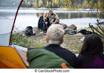 Couple Looking At Friends Resting In Tent
