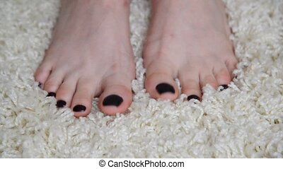 Womens feet are on beige carpet - Womens feet are on the...