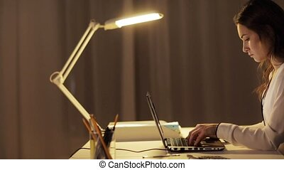 tired woman typing on laptop at night office - business,...