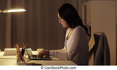 woman with laptop drinking coffee at night office -...