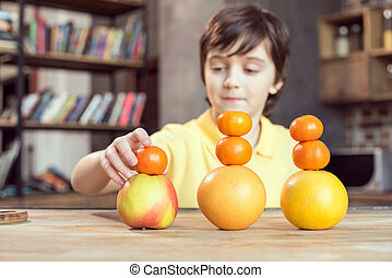 little boy playing with fresh fruits on table