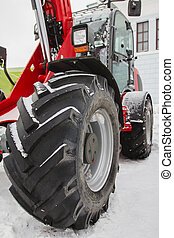 Agricultural tractor at winter snow day, close up