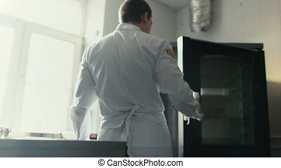 Professional chef man take off meat dish from oven at...
