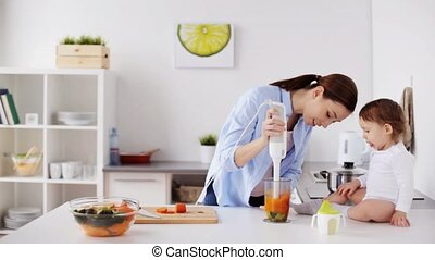 mother with blender cooking baby food at home - family,...