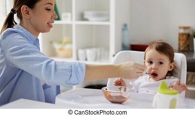 mother feeding baby with puree at home - family, food,...
