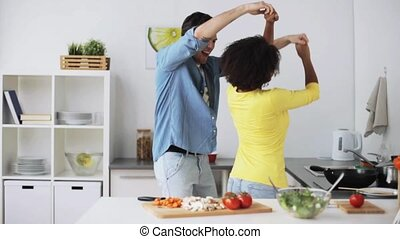 happy couple cooking food and dancing at home - cooking,...