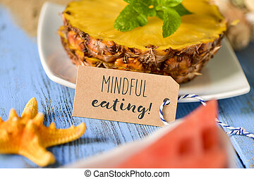 pineapple, watermelon and text mindful eating - a brown...