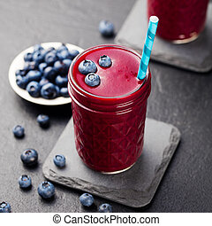 Berry smoothie with fresh blueberries on a black stone background. Copy space.