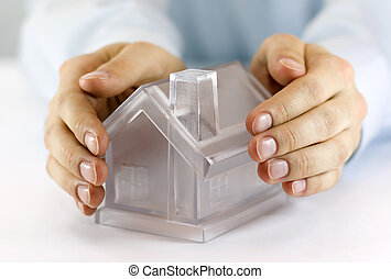 Protect Your House - Hands covering a model home