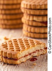 Several biscuits with red homemade marmalade on light wooden...