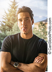 Young man sticking out tongue - Attractive young man doing...