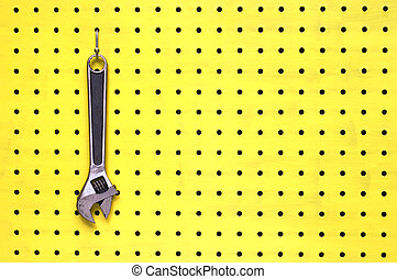 One adjustable wrench hangs from a hook on yellow pegboard -...