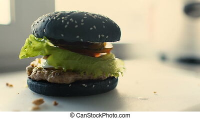 Closeup of professional made beef black burgers with lettuce and mayonnaise served on cutting board