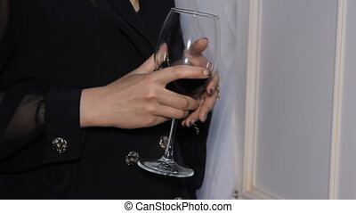 A Glass of Red Wine in the Hands