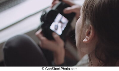 Female photographer reviewing photos on her camera - Back...