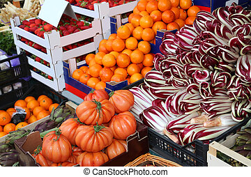stall of greengrocer with tomatoes radicchio oranges and...