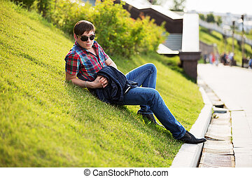 Young fashion man in sunglasses sitting on the grass in a city park