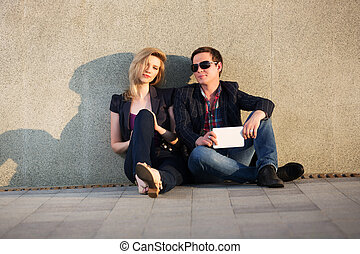 Young fashion couple with tablet computer sitting at the...