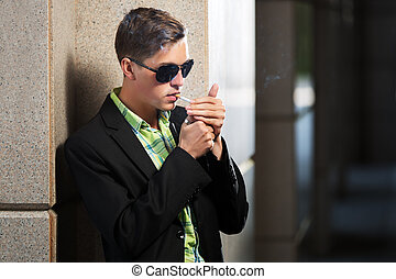 Young fashion man in sunglasses smoking a cigarette