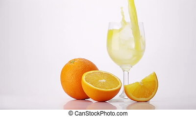 Pouring Orange Juice Into Glass. Light Background. Slow...