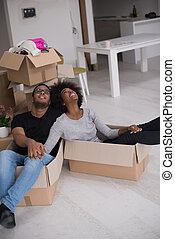 African American couple playing with packing material -...