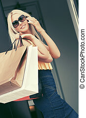 Happy fashion woman with shopping bags calling on mobile...