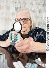 Grandma using magnifying glass to determine pill name -...
