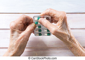 Senior woman hands taking out pill