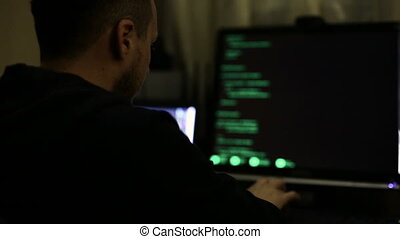 Hacker working at night, trying to break into system,...