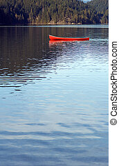 Empty canoe on lake - One red canoe floats empty on a...