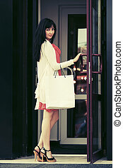 Young fashion woman with shopping bags at the mall doorway