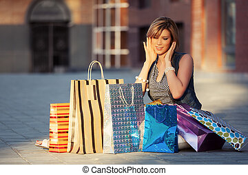 Happy young fashion woman with shopping bags sitting on a...