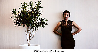 Black woman smiling at camera while standing next to plant -...