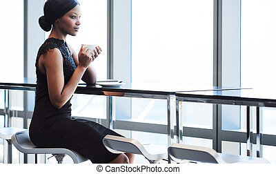 black woman sitting on bar chair next to large window - Wide...
