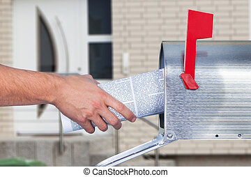 Man removing a newspaper from his mailbox with a closeup of...