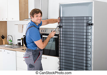 Serviceman Working On Fridge With Screwdriver