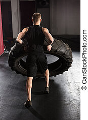 Rear View Of A Man Pushing Tire - Rear View Of A Young...
