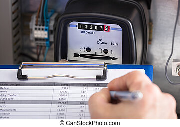 Technician Writing Reading Of Meter On Clipboard - Close-up...
