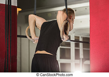 Man Pulling Up On Gymnastic Rings