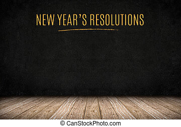New year's resolutions gold text on blackboard wall on wood...