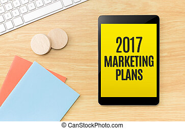 Top view of 2017 marketing plans on screen tablet with blue...